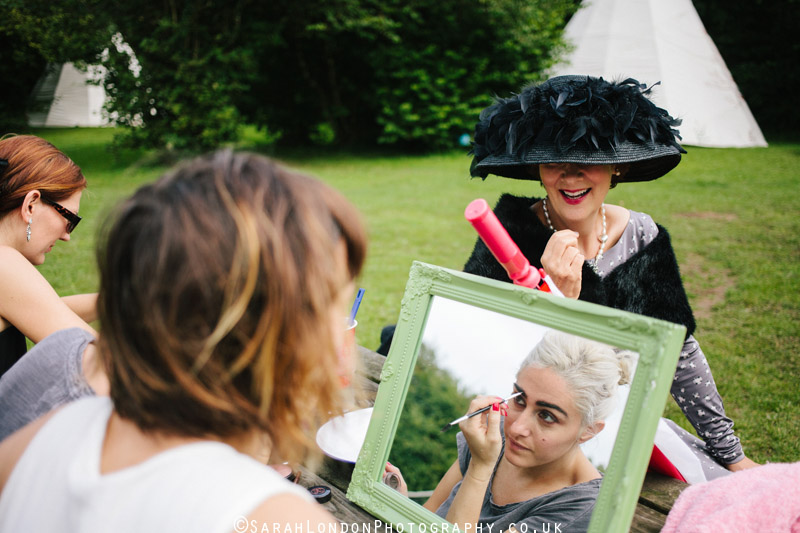 Wedding guests put their makeup on in a tipi field