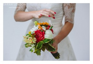 Autumn bridal bouquet being held by the bride with bright red nail varnish.
