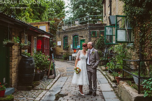 Couple kissing in cobbled street in Hackney city farm.