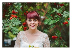 Portrait of the bride with red hair, red lips and red berries in the tree.