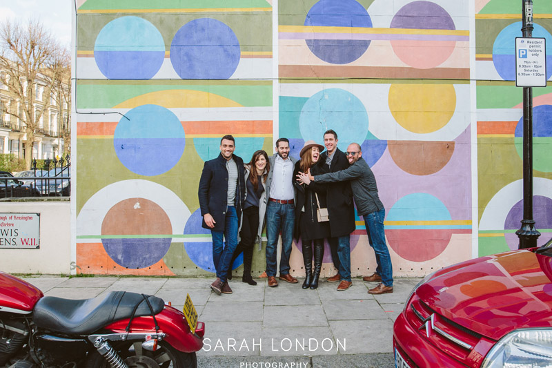 Portrait of a group of friends  in front of colourful wall in Notting Hill