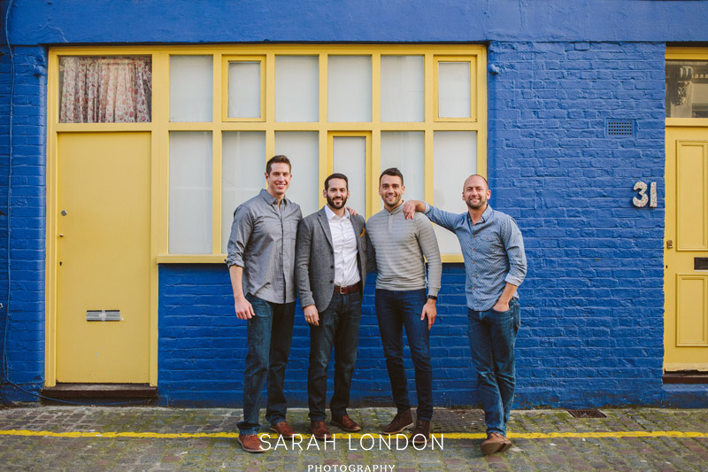 4 male friends pose for portrait in front of a blue and yellow house in Nitting hill