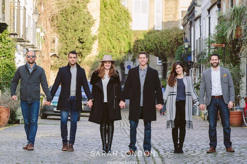Six friends stood still holding hands in a line in a Notting Hill muse