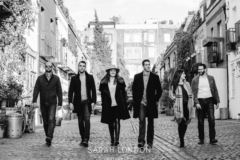 BW image of 6 friends walking along a Notting Hill Muse