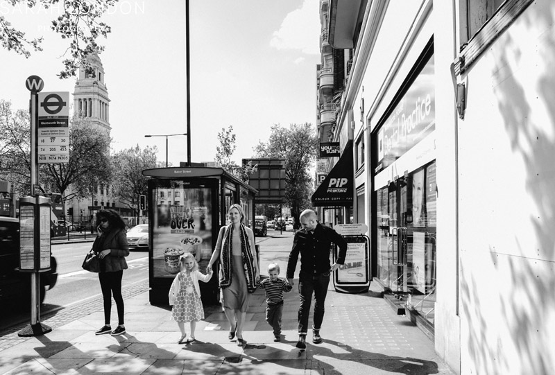 Black and White photo of a Family walking along hand in hand away from Marylebone Old Town Hall