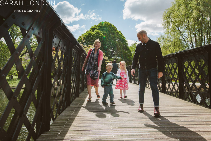 Mum, ada and two children walk along together across a small bridge