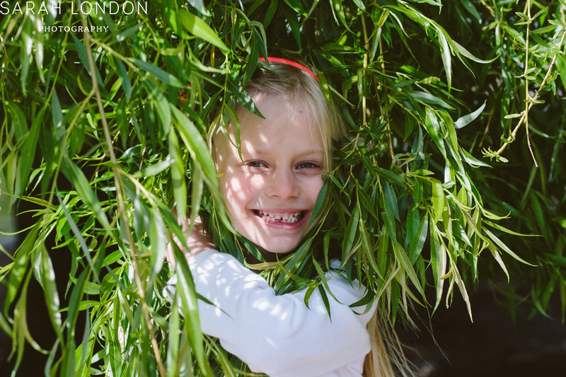 portraits of little girl hiding in a willow tree