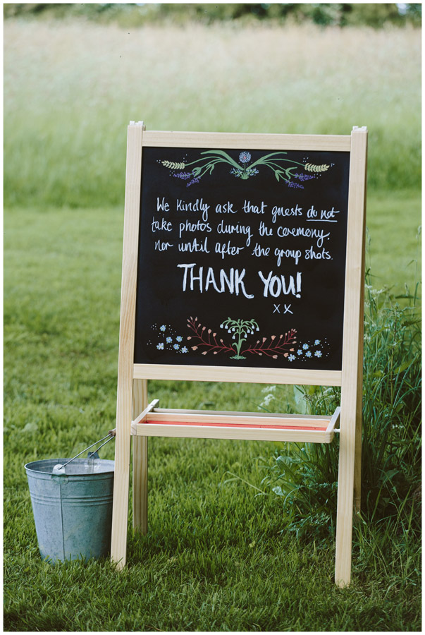 chalk board sign asking guests not to take photos during the ceremony