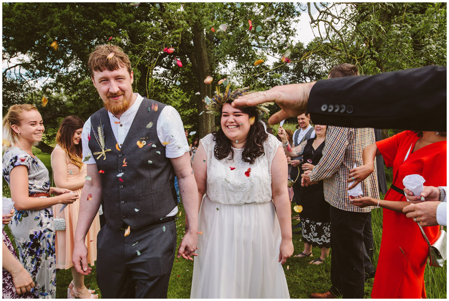 guest throwing confetti at bride and groom
