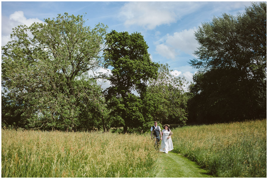 bride and groom walking hand in hand along a path through a meadow