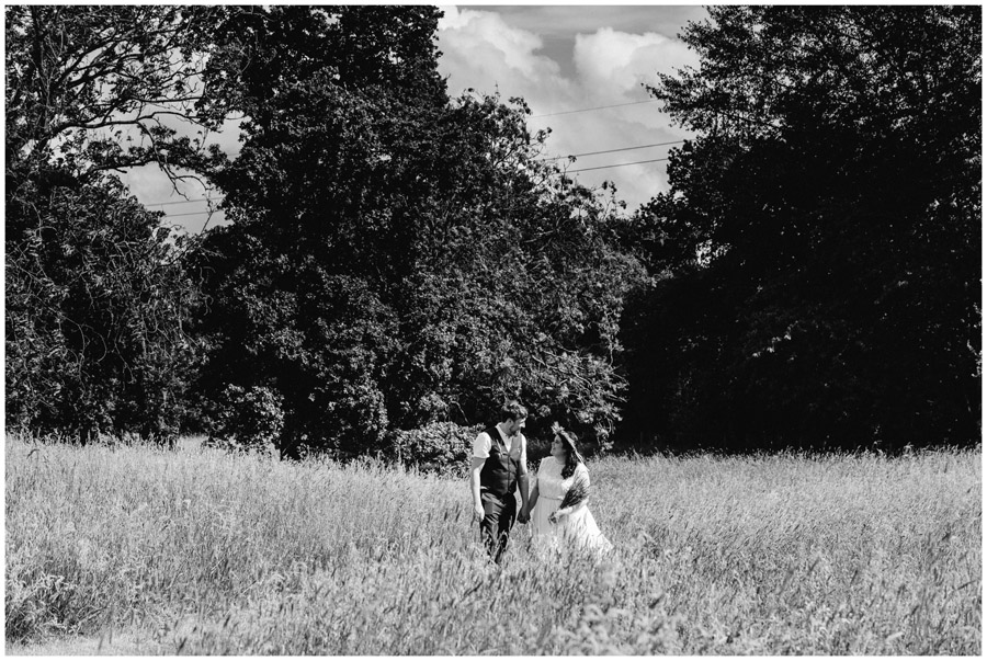 black and white of bride and groom walking through a field in wiltshire