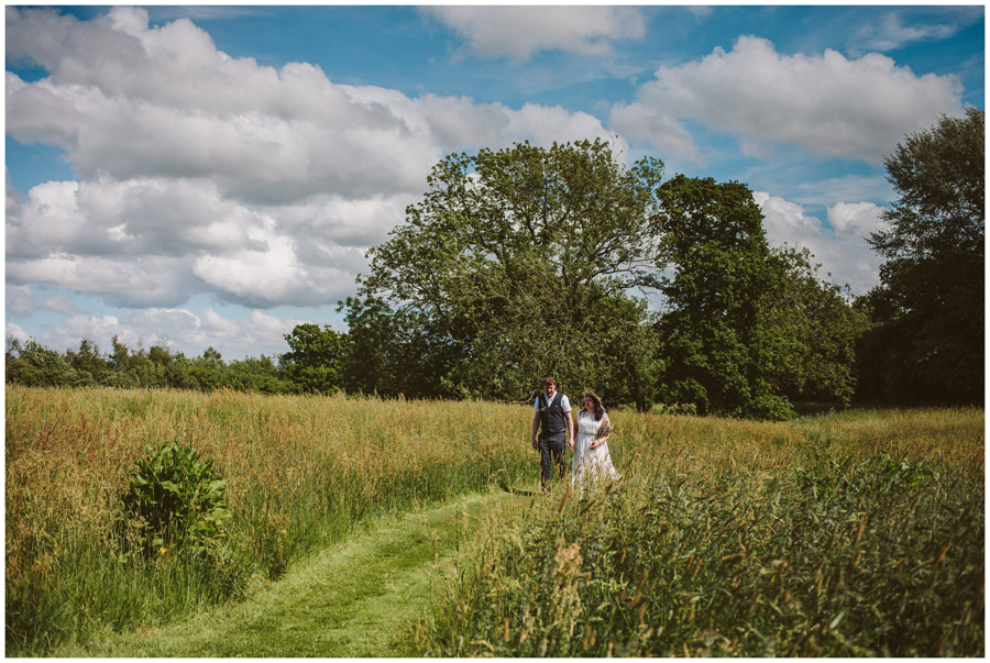 portrait of bride and groom walking through a meadow