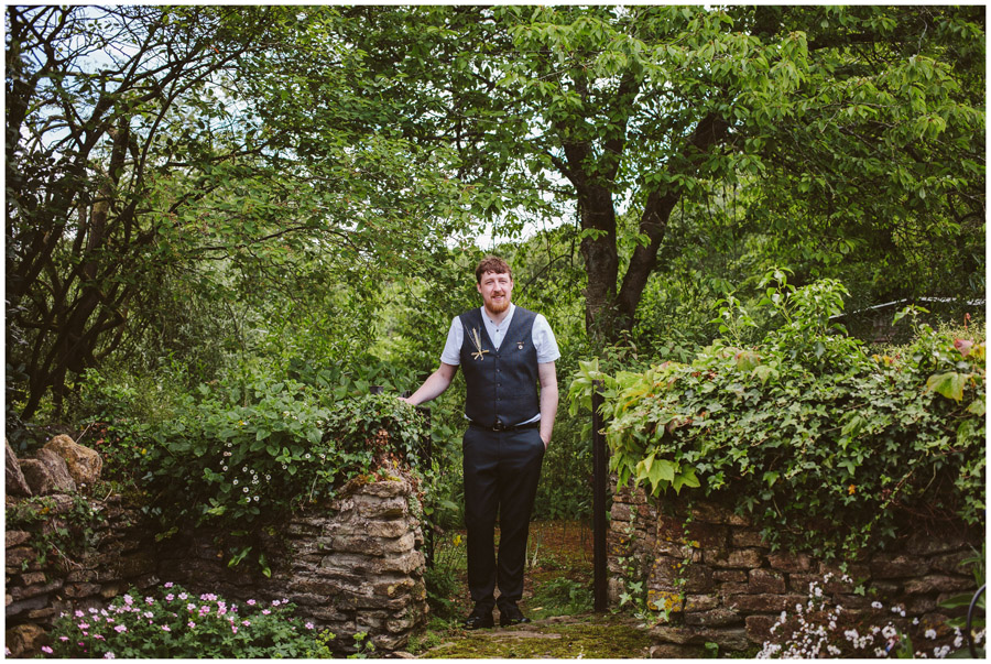 portrait of groom stood in gateway of flower garden at church farm