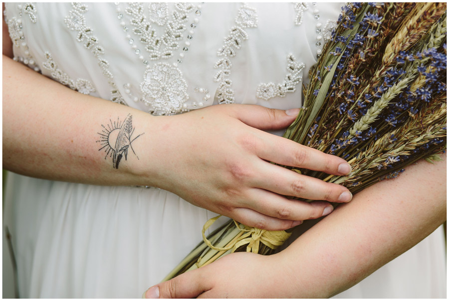 detail shot of brides hands holding corn and lavender bouquet with tattoo on wrist
