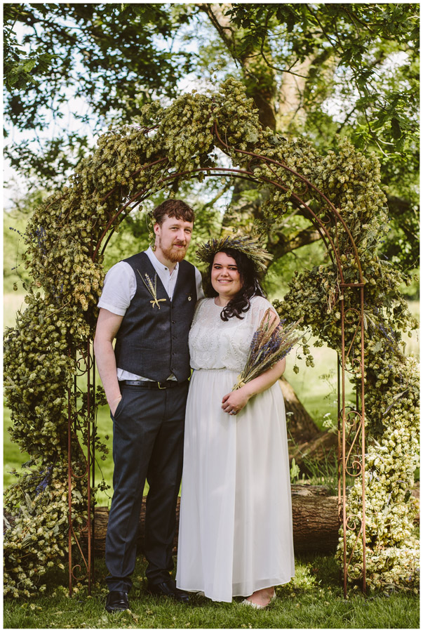 bride and groom portrait in wedding arch made of hops