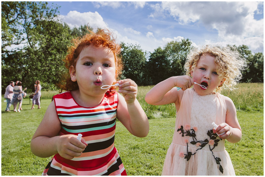 two little girls blowing bubbles to the camera