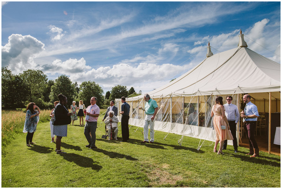 guests stand outside the marquee enjoying a drink