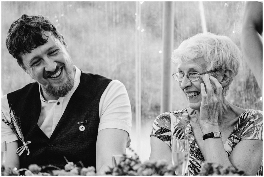 groom and mum laughing in BW image during speeches