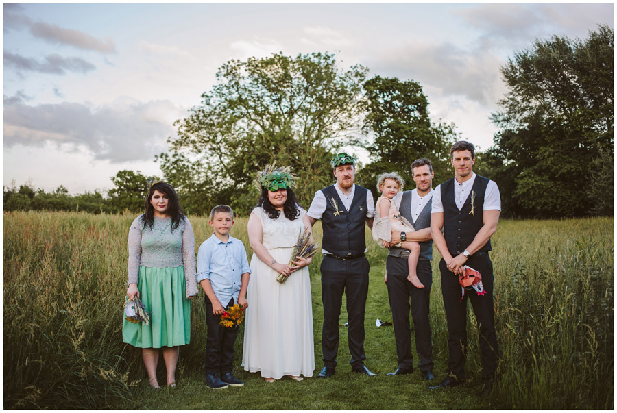 bridal party holding their masks stood in a meadow