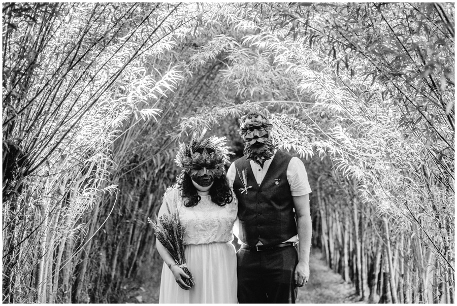 BW of bride and groom wearing masks in a willow tunnel