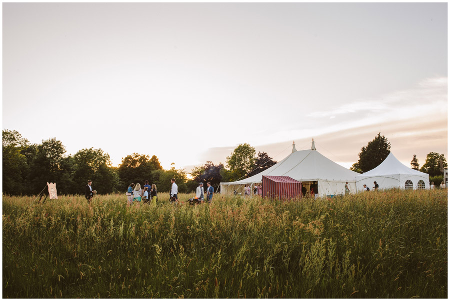 distance shot of wedding marquee in a meadow at sunset