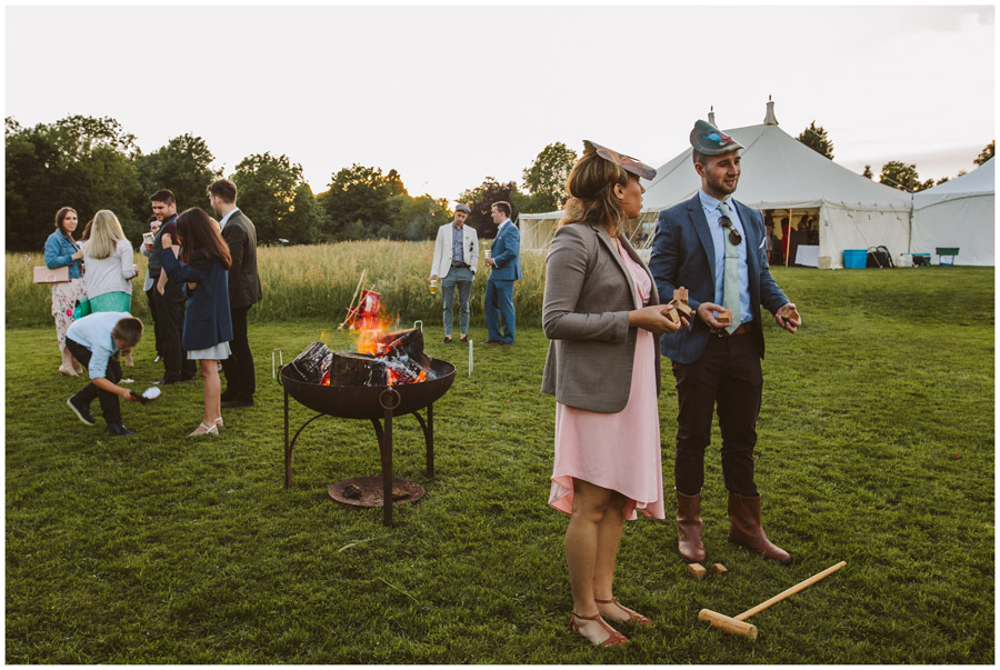 guests playing games in meadow with fire pit
