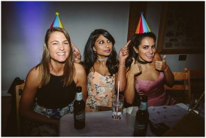 female wedding guests wear party hats