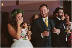 bride and groom laugh during speeches in lewes village hall