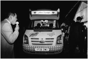 BW of ice-cream van and man eating ice-cream