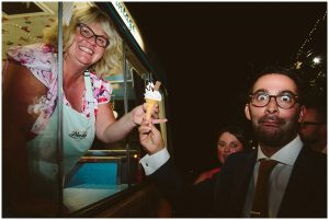 ice cream lady hands ice-cream to wedding guest pulling face