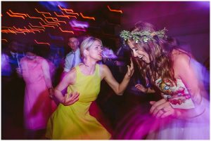 bride dances with friend at high hurstwood village hall