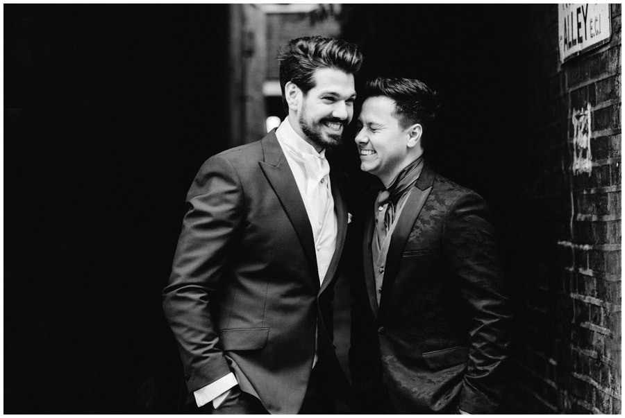 BW portrait two grooms in suits laughing