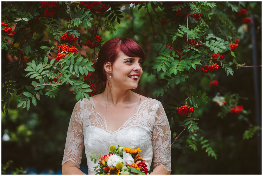 natural portrait of bride stood in tree with red berries