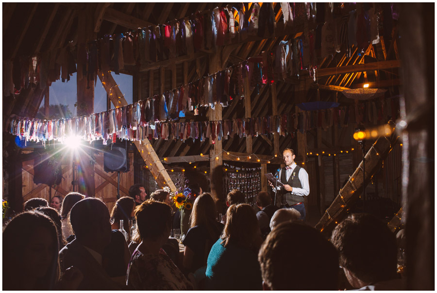 groom giving speech in dark sussex barn with flash directed on him