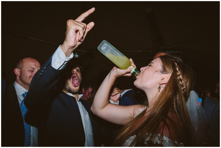 bride drinks from bottle on dance floor