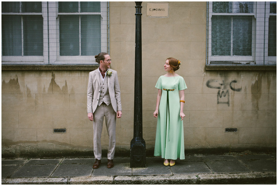 vintage bride and groom stood side by side on a pavement in Brighton
