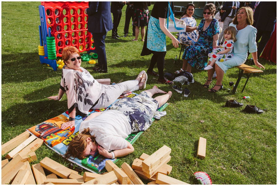 wedding guests relax on grass during reception