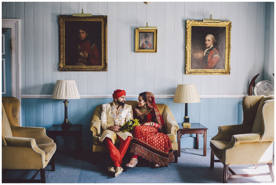 portrait of bride and groom in traditional indian wedding dress sat casually chatting