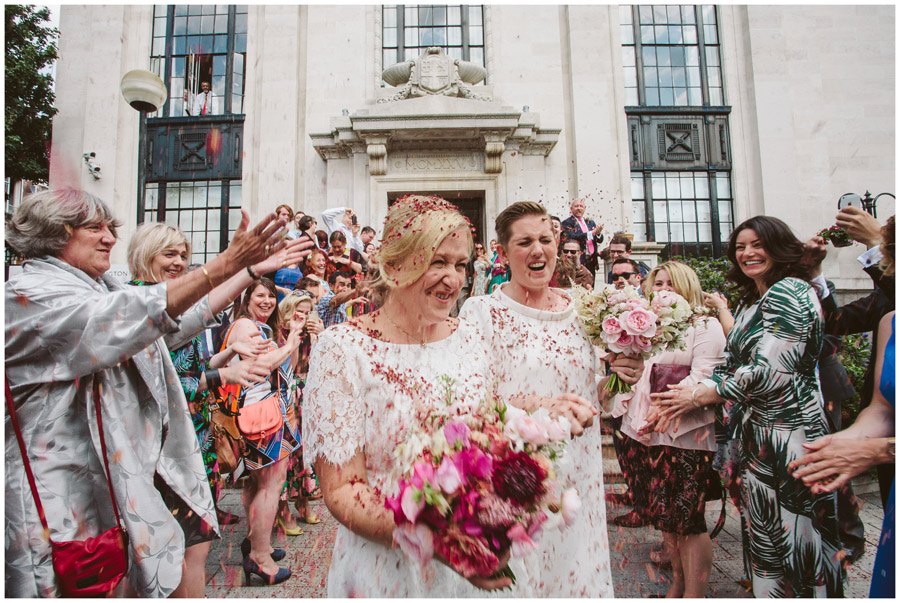 two brides being pelted with natural petal confetti by wedding guests in Brighton