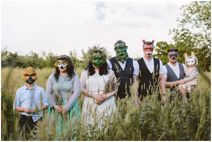 bride and groom with their bridal party all wearing masks inspired by folklore