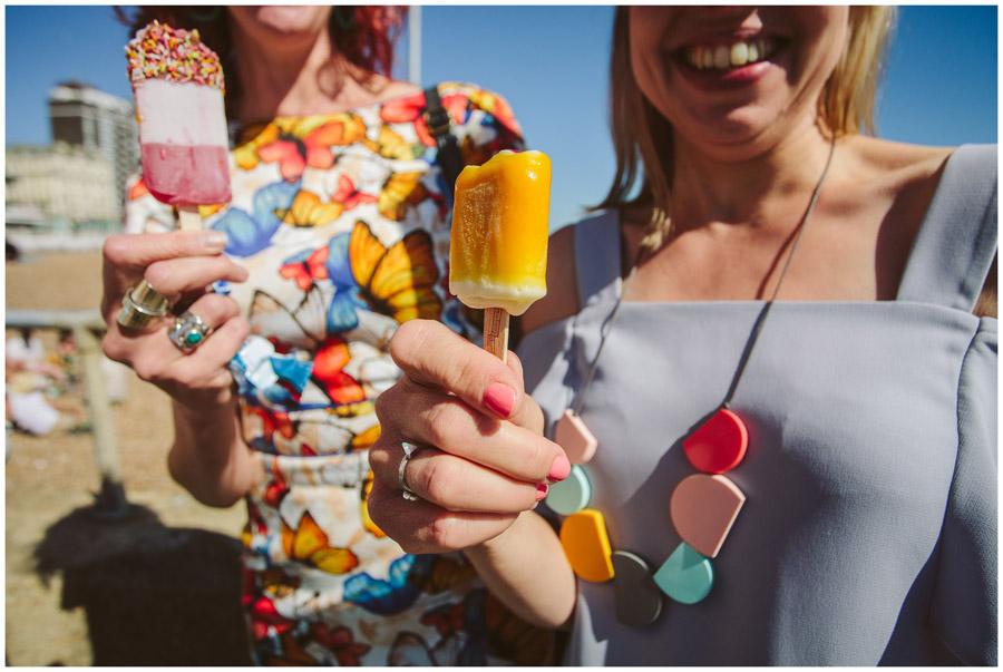 fun shot of wedding guests eating ice-cream on Brighton beach