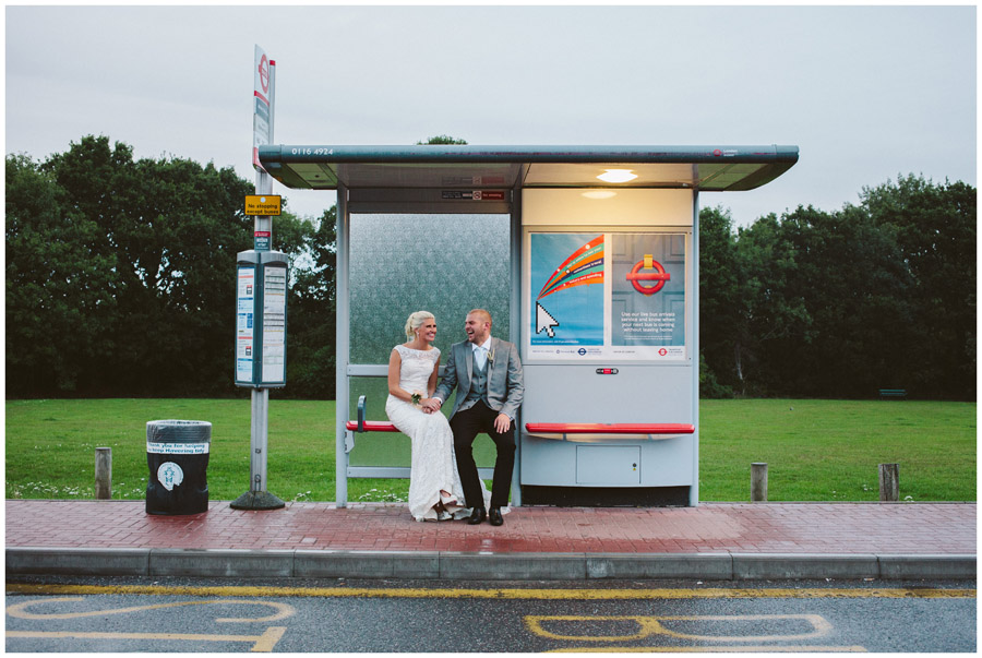 bride and groom sitting at bus stop in the rain laughing