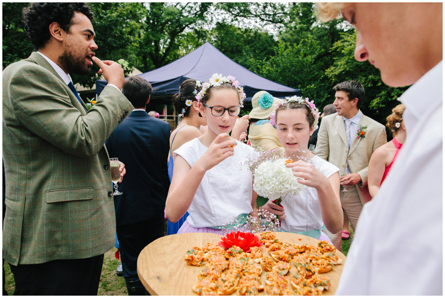 documentary image of two flower girls eating canapés